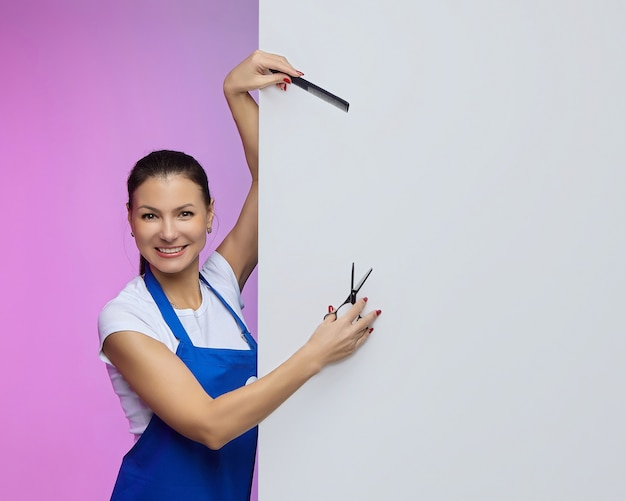 Estilista de cabeleireiro de aparência asiática posa com um outdoor branco. conceito de publicidade