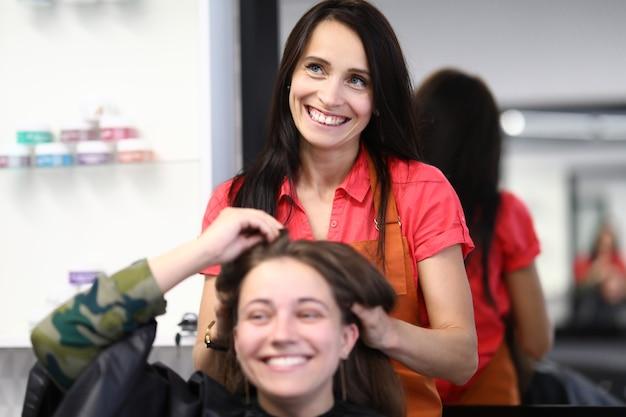 Estilista de cabeleireiro segura o cabelo da cliente em salão de beleza