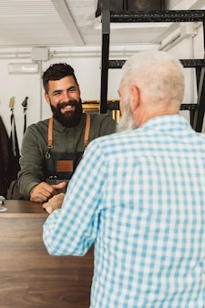 Estilista de cabelo barbudo sorridente conversando com o cliente idoso no salão