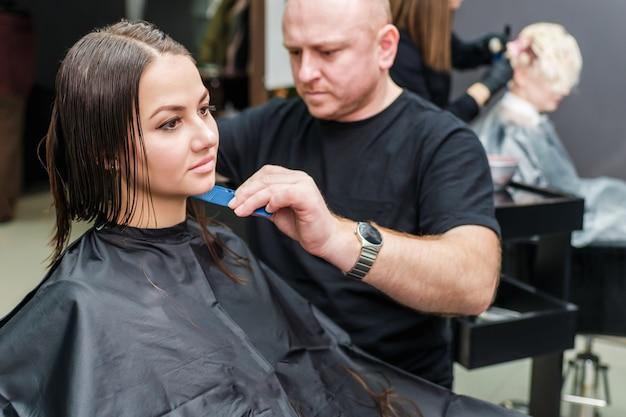 Estilista de cabelo está fazendo novo penteado no salão de cabeleireiro.