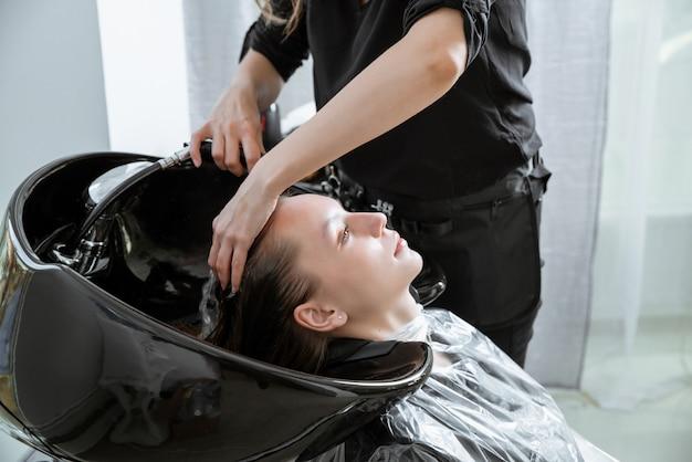 Estilista de cabelo lavando o cabelo da menina loira yong no salão de beleza antes do corte de cabelo