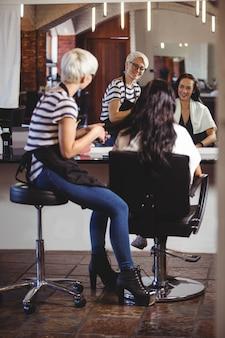 Estilista de cabelo sentado com o cliente no salão de cabeleireiro