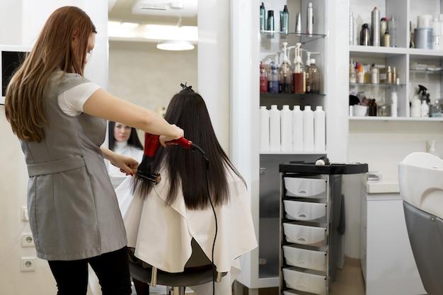 Estilista de cabelo trabalha no penteado de mulher no salão. secagem de cabelos castanhos compridos com secador de cabelo e escova redonda