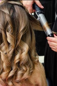 Estilista de fazer um penteado com modelador de cabelo. conceito de salão de beleza