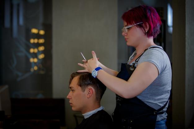 Estilista de garota faz um corte de cabelo de um cara jovem em um salão de beleza.