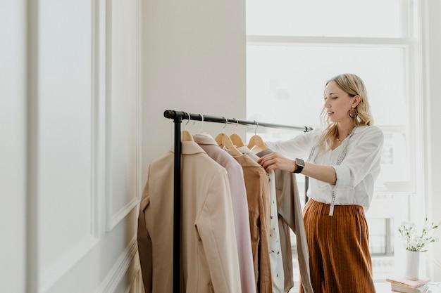 Estilista de moda classificando o cabide de roupas