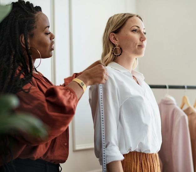 Estilista de moda medindo os ombros de uma cliente