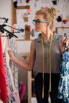 Estilista de moda procurando o vestido perfeito
