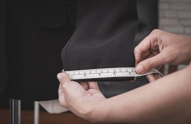 Estilista de roupas está medindo a manga do casaco