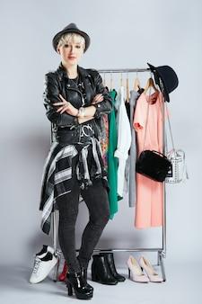 Estilista em roupa da moda em pé perto de vestidos na prateleira, corpo inteiro. pessoa na esfera da moda, escolhendo roupas, olhando para a câmera. compras, dentro de casa, compra de roupas