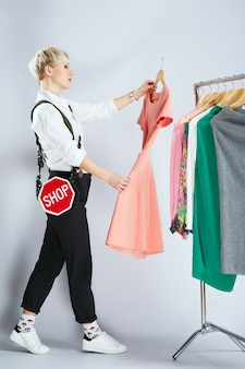 Estilista em roupa da moda examinando vestidos na prateleira, corpo inteiro. pessoa na esfera da moda, escolhendo roupas. compras, interior, perfil