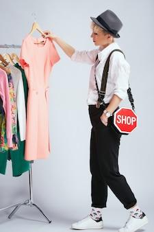 Estilista em roupa da moda examinando vestidos na prateleira, corpo inteiro. pessoa na esfera da moda, escolhendo roupas, mulher loira na moda. compras, interior, perfil