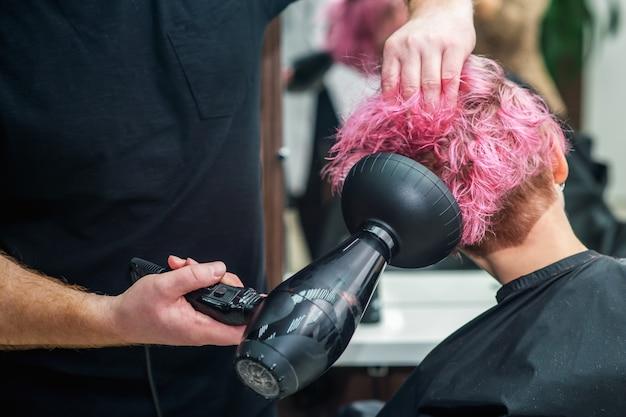 Estilista está secando o cabelo da mulher.