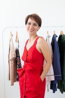 Estilista feminina perto de rack com cabides. conceito de compras, designer de roupas e consumismo.