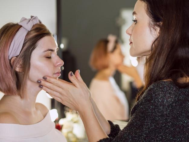 Estilista massageando o rosto do cliente