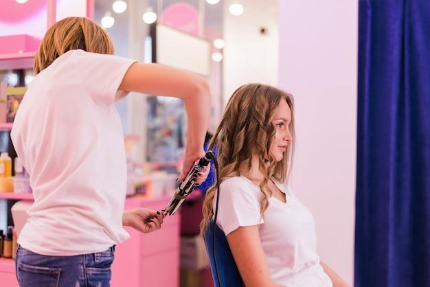 Estilista ondulando o cabelo para mulher de cabelo castanho no salão. menina se preocupa com seu penteado