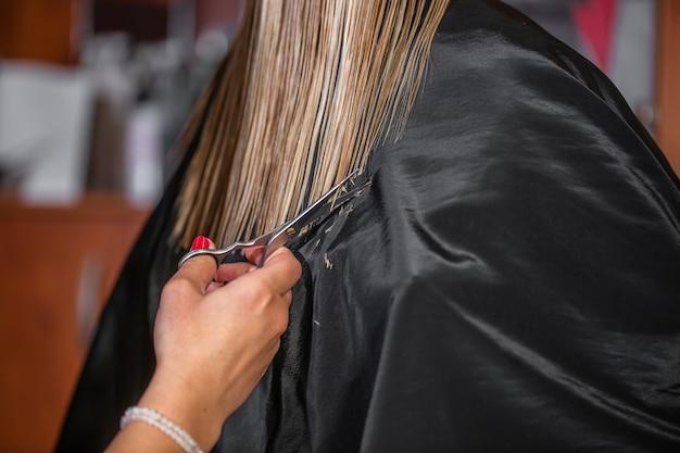 Estilista profissional aparando o cabelo no estúdio de cabeleireiro