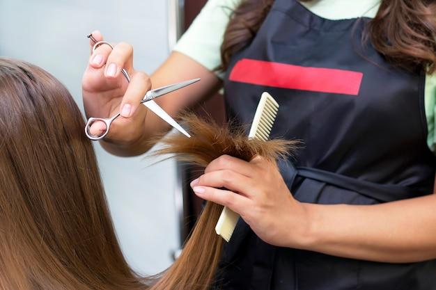 Estilista profissional corta cabelo feminino em salão