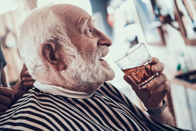 Estilista profissional tesoura homem mais velho na barbearia
