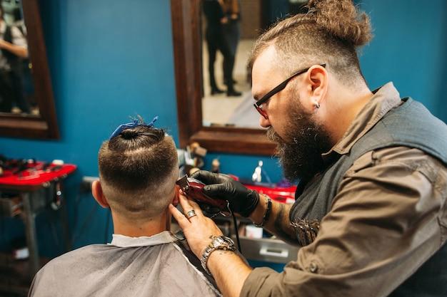 Estilista raspando cabeça de homem em barbearia