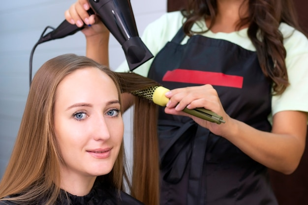 Estilista secando o cabelo da cliente com um secador e uma escova redonda