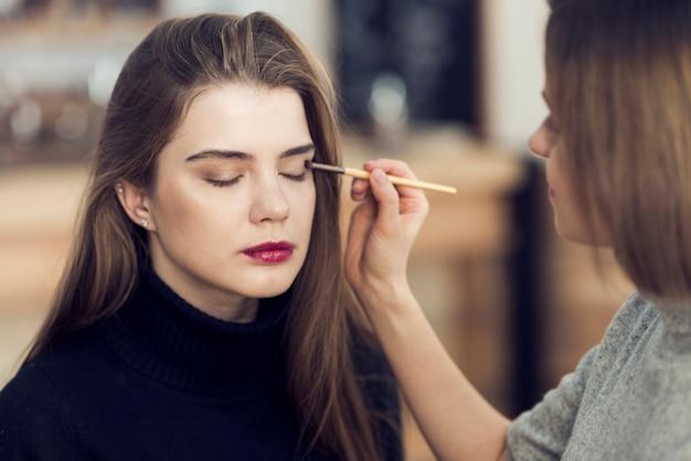 Estilista trabalhando com lindo modelo