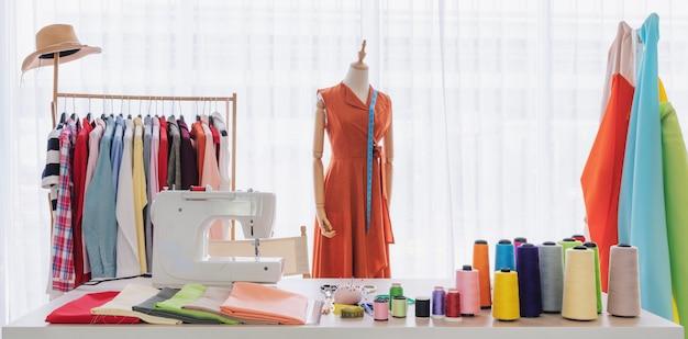 Estilista trabalhando estúdio, com itens de costura e materiais na mesa de trabalho
