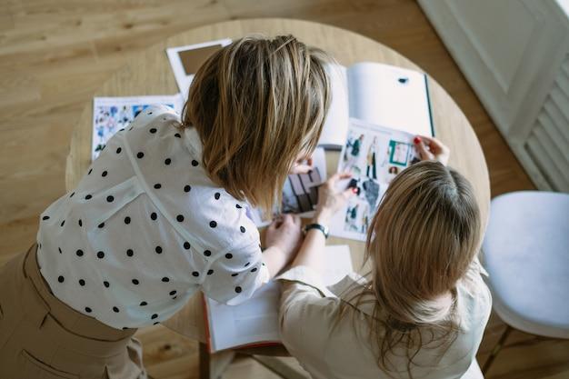 Estilistas de designers de moda, trabalhando em um novo projeto no estúdio, usando revistas, esboços. dois jovem sorrindo discutindo idéias. vista do topo