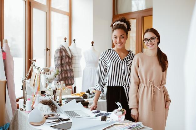 Estilistas de duas mulheres no estúdio de design. processo de trabalho de modelagem de roupas novas. mulheres africanas e brancas de óculos olhando para a câmera