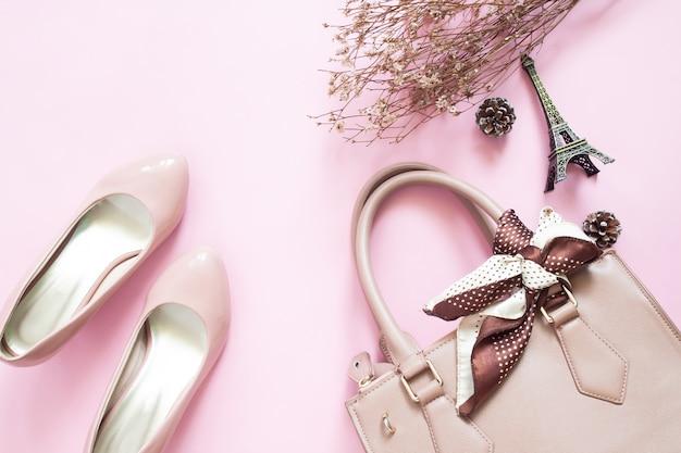 Estilizado feminino plana leigos com sapatos, bolsa de mão e flores na cor rosa vista superior.