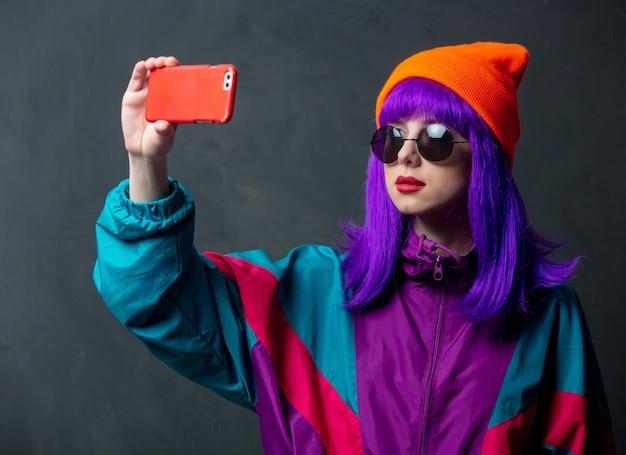 Estilize uma mulher em um terno esporte e óculos de sol usando o celular na parede escura
