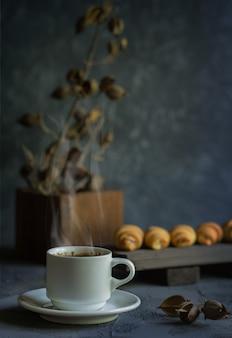 Estilo antigo ainda vida com croissants e uma xícara de café quente