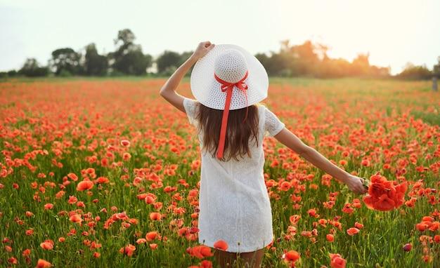 Estilo ao vivo de mulher jovem e bonita possui chapéu branco de mãos e fica de braços abertos no campo de papoulas vermelhas.