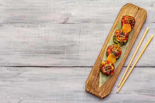 Estilo coreano pepinos recheados. kojori kimchi lanche picante. legumes fermentados e marinados. fundo de madeira