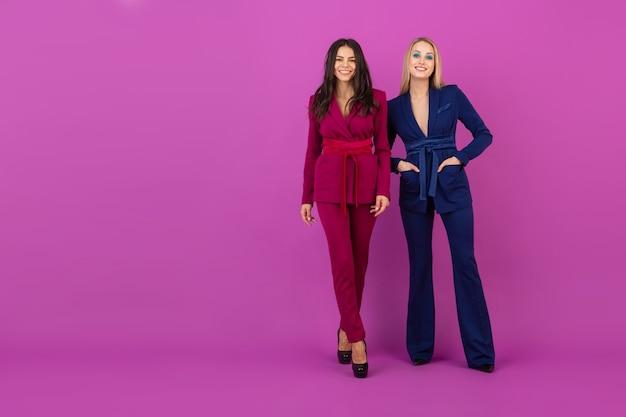 Estilo de alta costura duas mulheres atraentes sorridentes na parede violeta em elegantes ternos coloridos de cor roxa e azul, amigos se divertindo juntos, tendência da moda