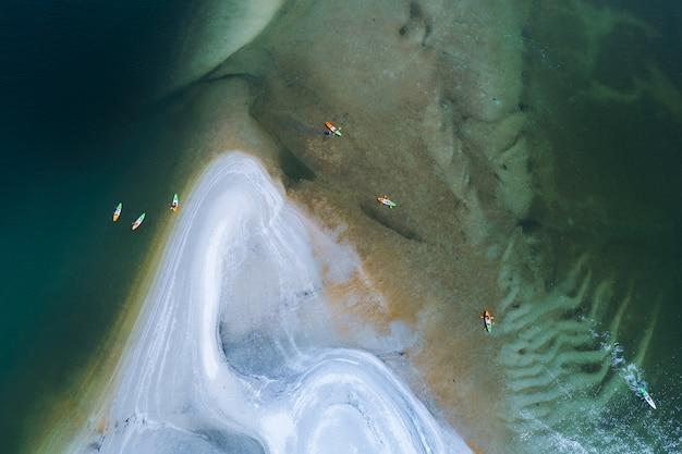Estilo de aventura de turistas de caiaque no mar e vista superior aérea de praia branca abstraem base