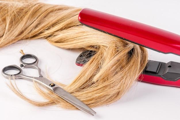 Estilo de cabelo. closeup mulher loira de cabelos compridos fazendo penteado de ferro. conceito de cabelo danificado, tesoura.