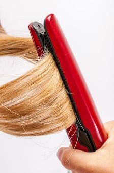Estilo de cabelo. closeup mulher loira de cabelos compridos fazendo penteado penteado com alisador de cabelo elétrico