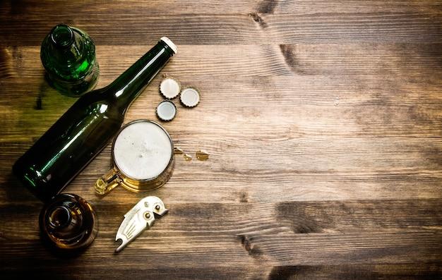 Estilo de cerveja - garrafa, cerveja no copo e tampas na mesa de madeira