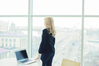 Estilo de chefe de mulher trabalhando em um escritório em um laptop mãos