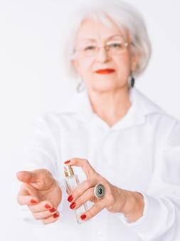 Estilo de moda mulher sênior. tendências de perfume. frasco de fragrância cara em mãos femininas.