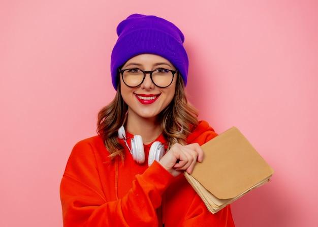 Estilo de mulher com fones de ouvido e livros na parede rosa