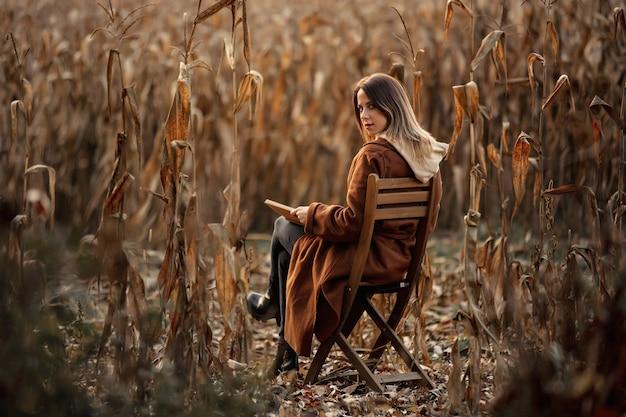Estilo de mulher com livro sentado na cadeira no campo de milho na temporada de outono