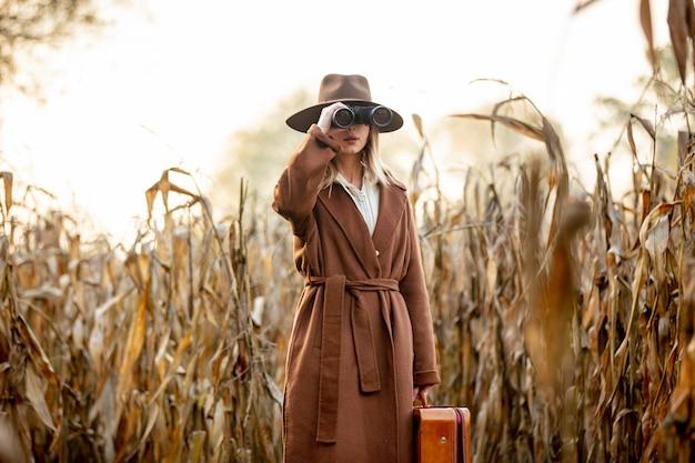 Estilo de mulher com mala de viagem e binóculos no campo de milho na temporada de outono