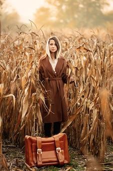 Estilo de mulher de casaco com mala no campo de milho na temporada de outono