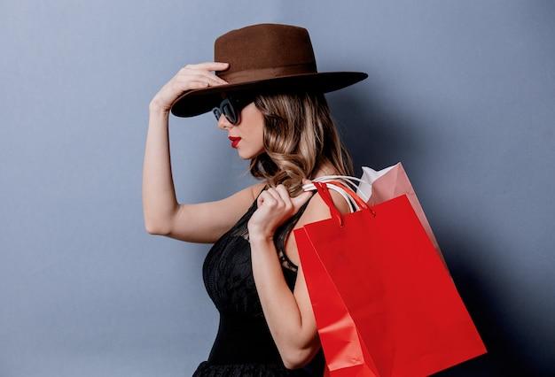 Estilo de mulher em óculos de sol com sacos de compras na parede cinza
