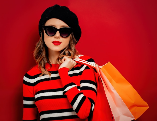 Estilo de mulher em óculos de sol com sacos de compras na parede vermelha