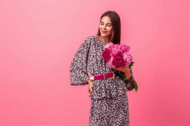 Estilo de mulher em vestido com flores em fundo rosa