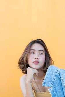Estilo de retrato de uma mulher no fundo da parede amarela