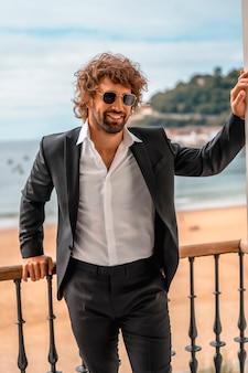 Estilo de rua com um jovem homem caucasiano de cabelos escuros em um terno preto e uma camisa branca em um hotel de luxo, com óculos de sol, editorial de moda. encostado na janela sério com o mar atrás